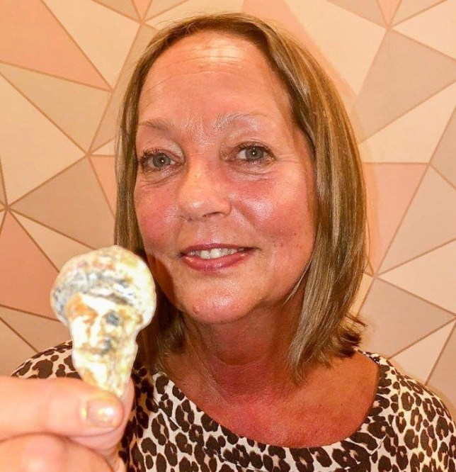 Debra showing off her seashell she found while on an evening walk with her husband (Picture: SWNS)