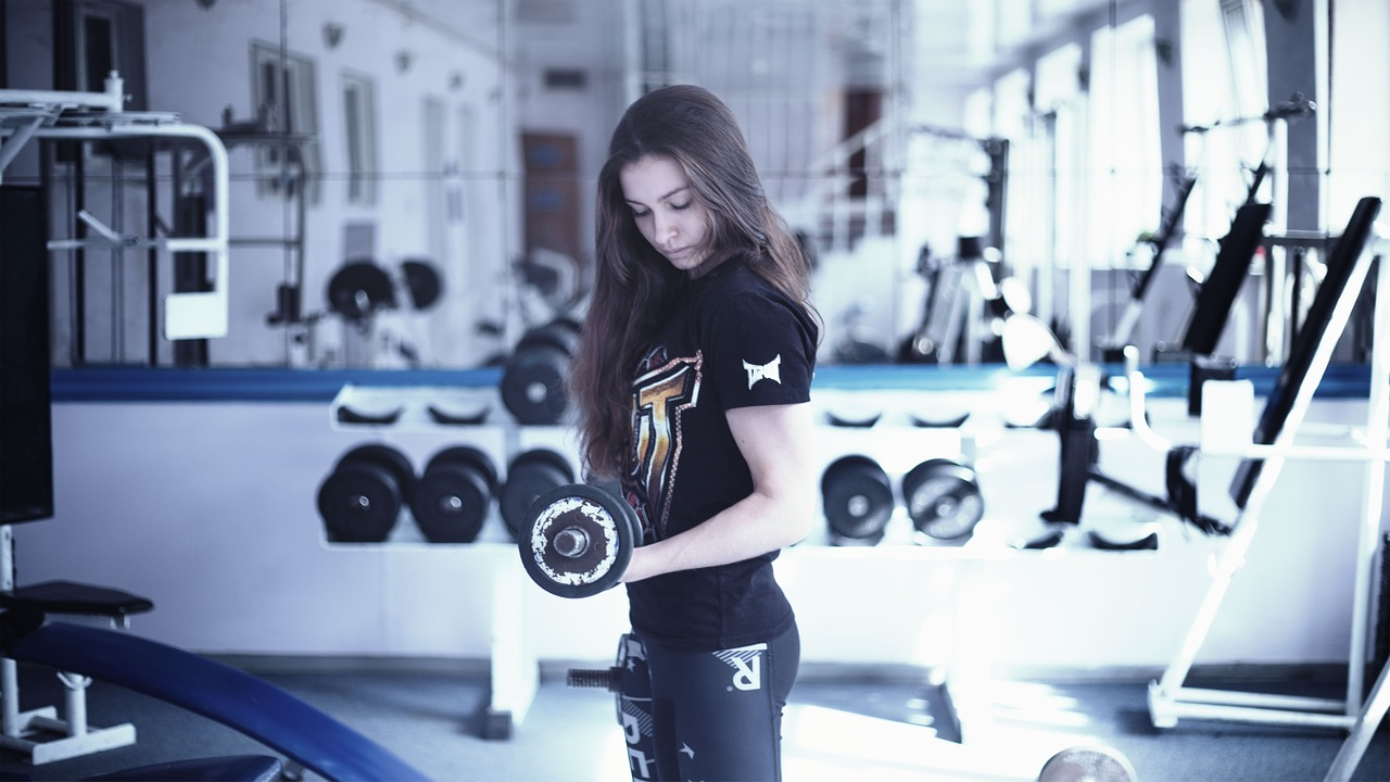 Girl doing bicep curl in the gym