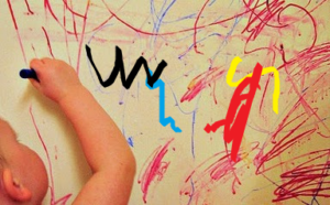 toddler using a marker to write on the wall
