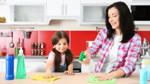 mom and daughter cleaning the kitchen