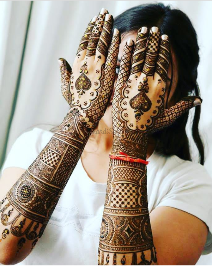girl showing photo of bridal Arabic mehndi design